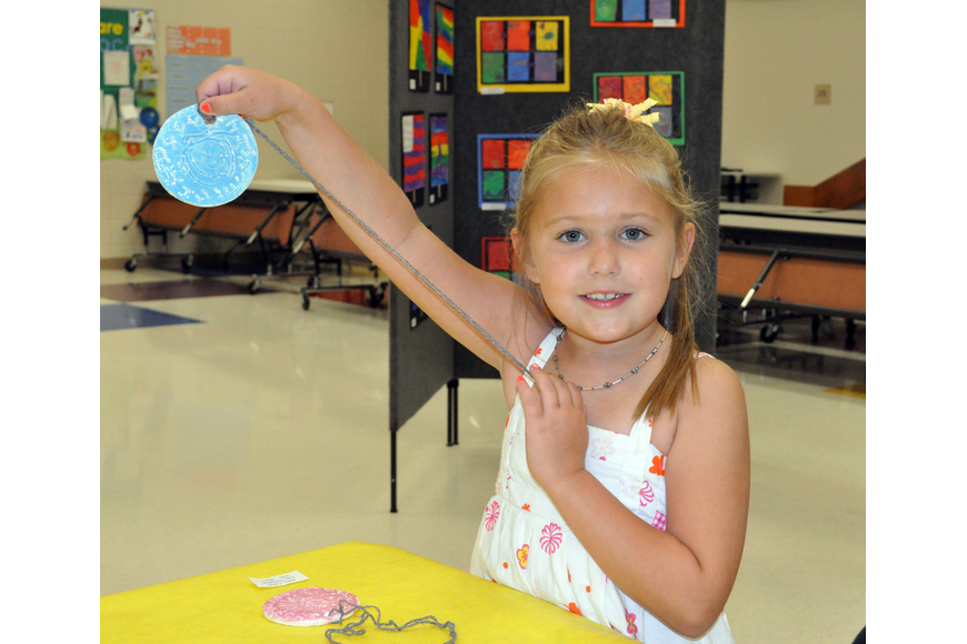 Kindergartener Alexis Schilling enjoyed painting her medallion.
