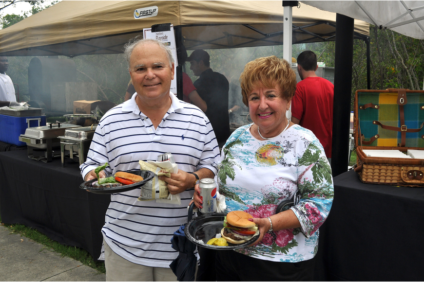 Steven Cohen and Helen Katz get hamburgers from the Mattison's booth, Friday, June 8, during Friday Fest at the Van Wezel.