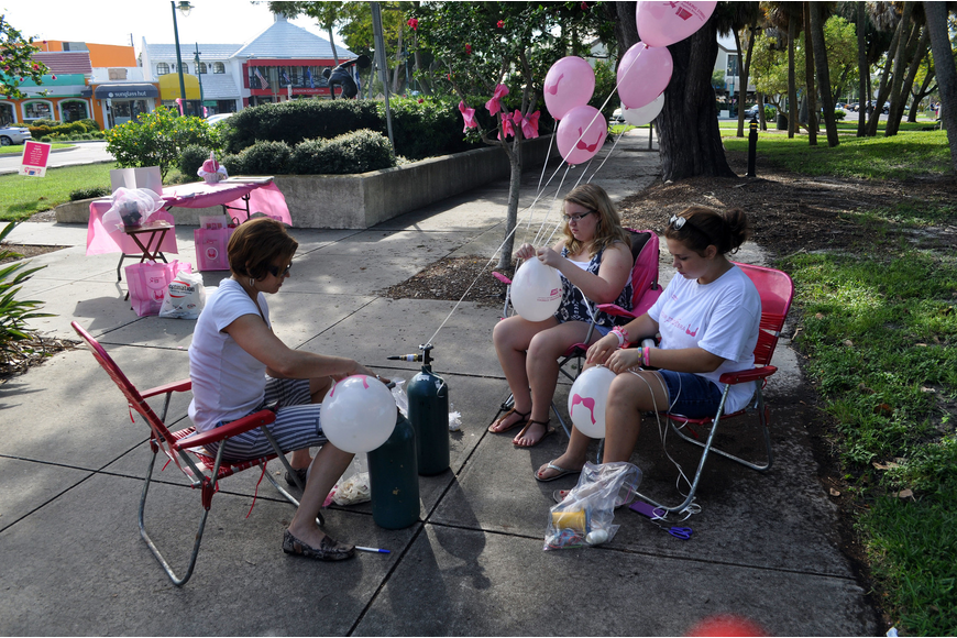Maria Lanzillotti, Megan Fowler, 14, and Melissa Hampton, 14, blow up and tie ribbons to balloons Saturday, Oct. 6, on St. Armands Circle as part of the Circle Me Pink event.