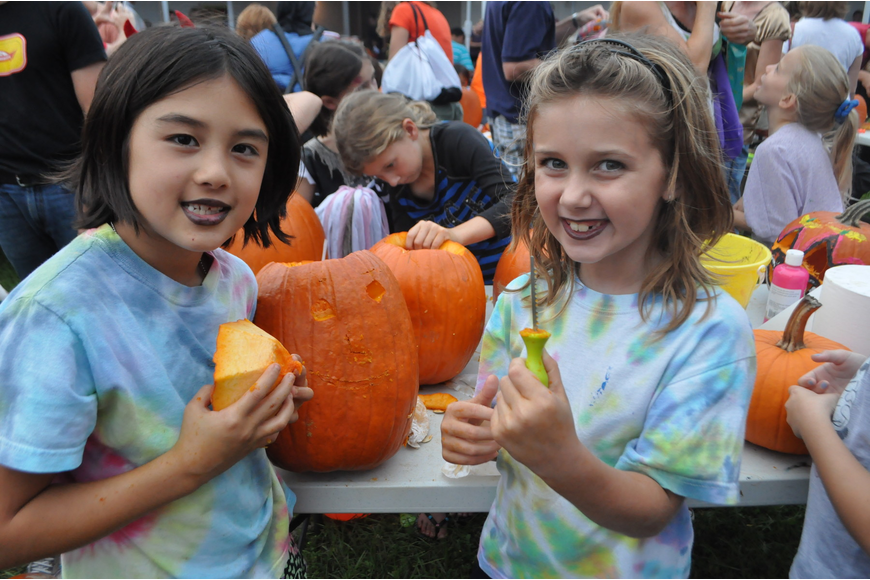 Avery Brum and Ella Emmett carve pumpkins.