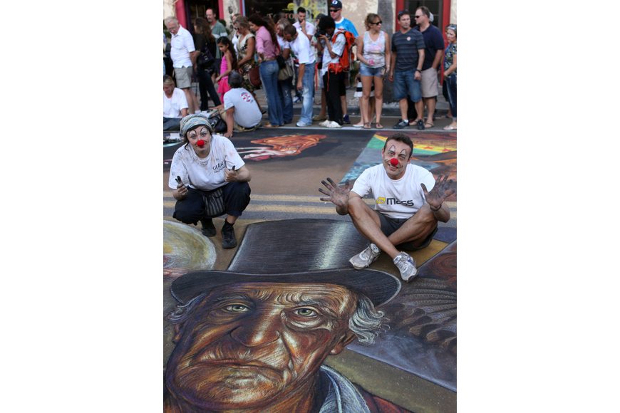 Vera Bugatti and Legno Luigi wear clown noses and show off their chalky hands as they pose with their piece Sunday, Nov. 4, during the Sarasota Chalk Festival.