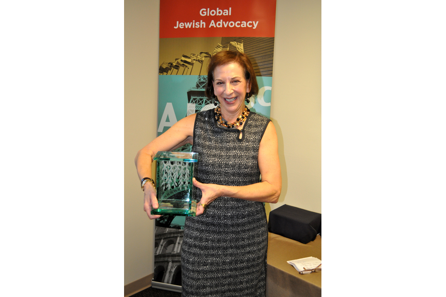 Former AJC West Coast Florida past president Sue Jacobson holds her Tzedakah box — a traditional Jewish box that the owner fills with lose change and eventually donates the change to charity.
