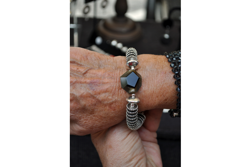 Leanne Boris tries on a bracelet made by Michael Dandren that features a large piece of agate.
