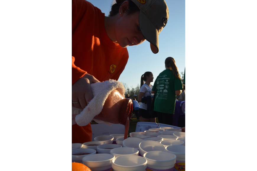 Abby Blow pours Smoothie King smoothies into little cups for racers and volunteers. Smoothie King was one of the sponsors of the event.