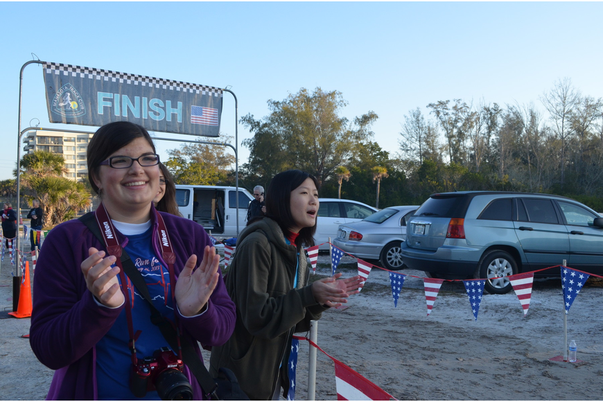 Fiorella Nicoloso and Christine Chern cheer runners on at the finish line.