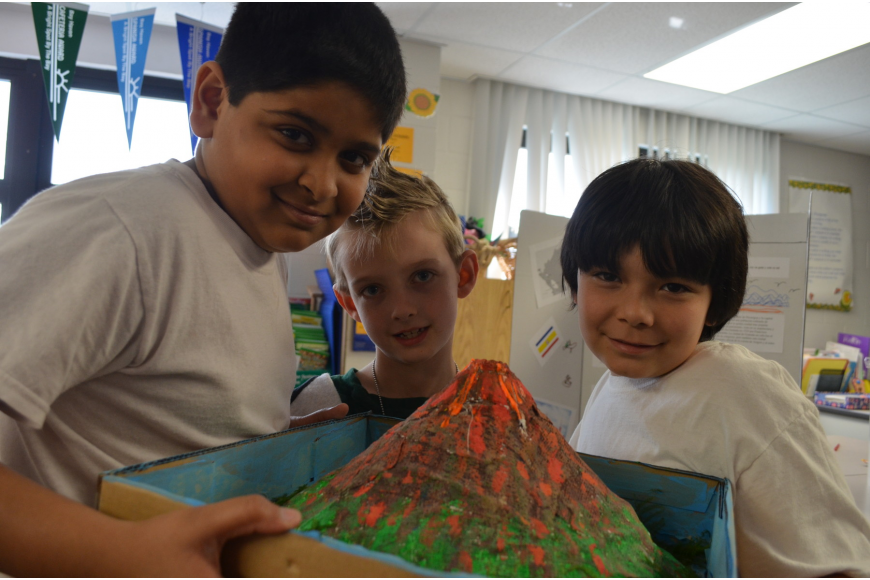Third graders Neel Patel and Jordan Calvillo made a volcano for their project and second grader Liam Holzler (middle) came to check it out.