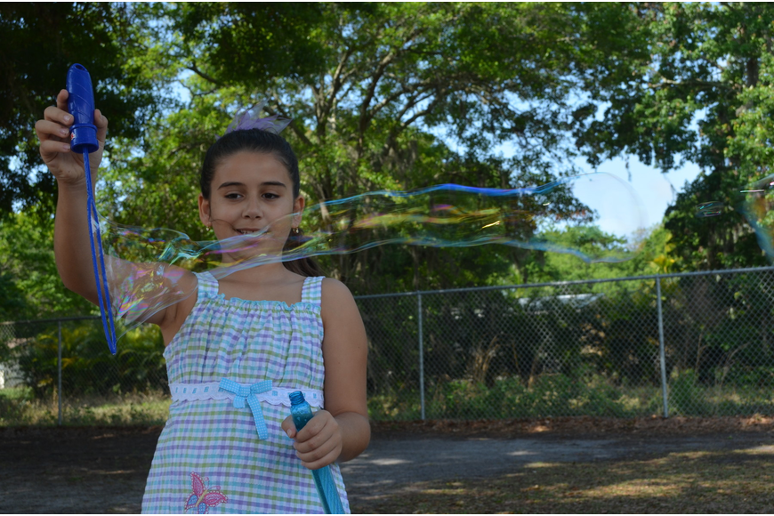 Ali Kaiser-Andradi plays with a magic bubble wand.