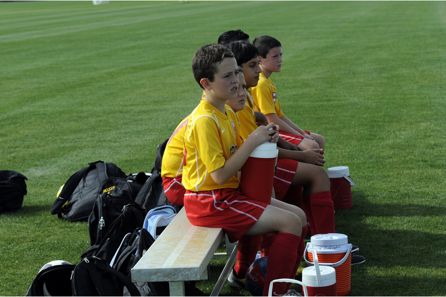 Members of the Lakewood Ranch Chargers U12 team look on as their teammates battle Strictly Soccer April 13.