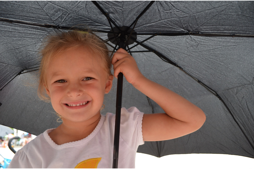 Madelyn Marsters, 4, hides under an umbrella as rain pours down on the parade.