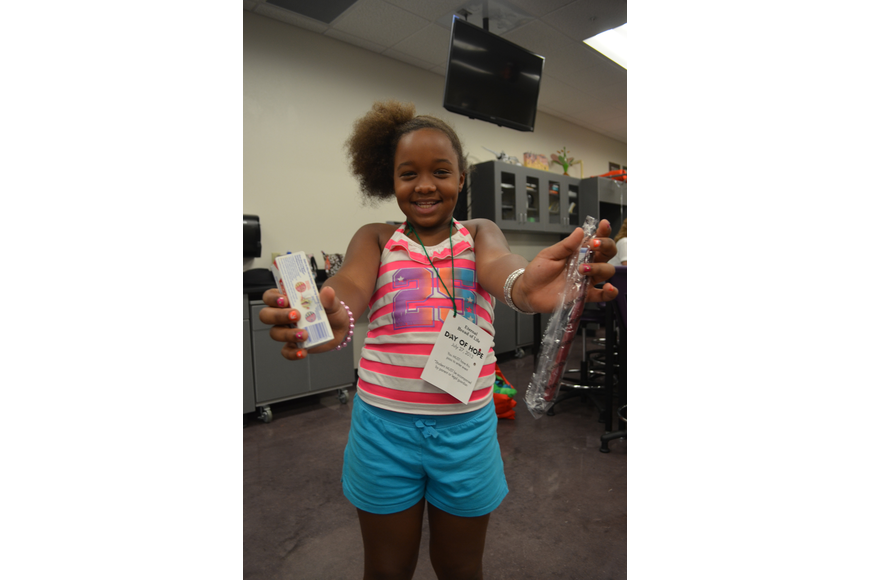 Tanityah Gipson, 9, gets a goody bag with a toothbrush and toothpaste. She got her teeth checked and fluoride put on them at the Fifth Annual Day of Hope. Taniyah will be back at Tuttle Elementary in August.