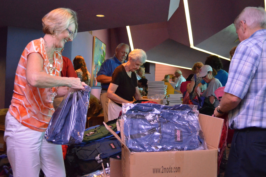 Volunteers on one side of the table prepare the supplies for the backpacks.
