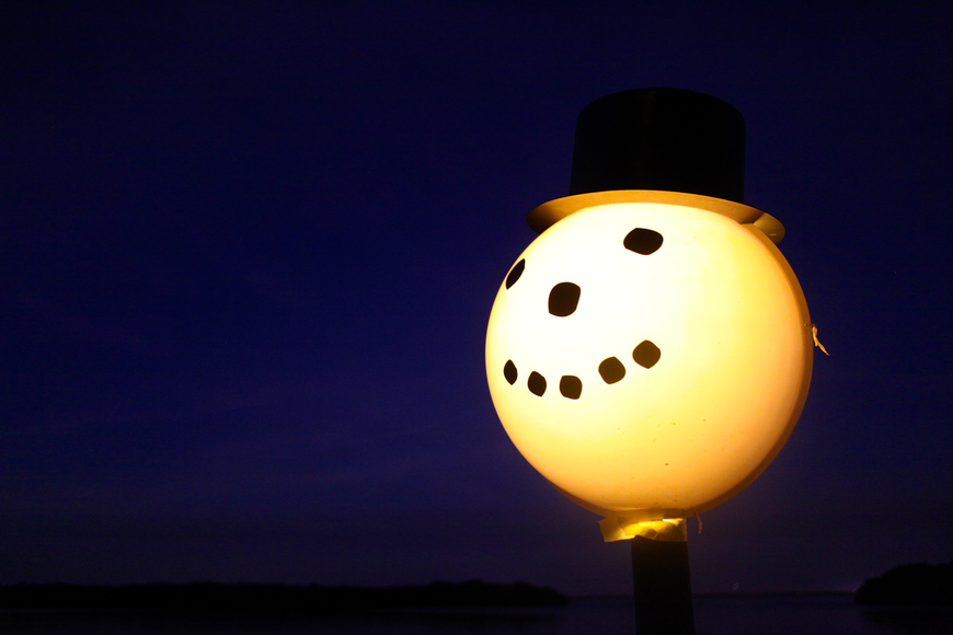 A light along the pathway is decorated as a snowman.