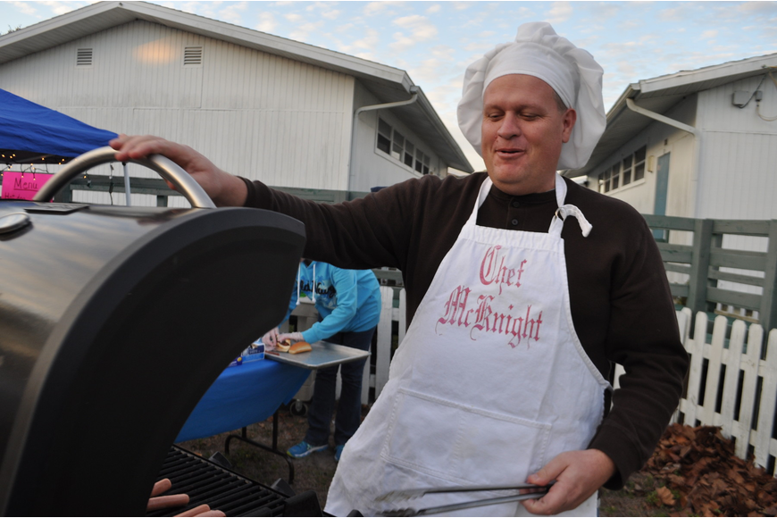 Principal Steve Royce cooks hot dogs for guests.