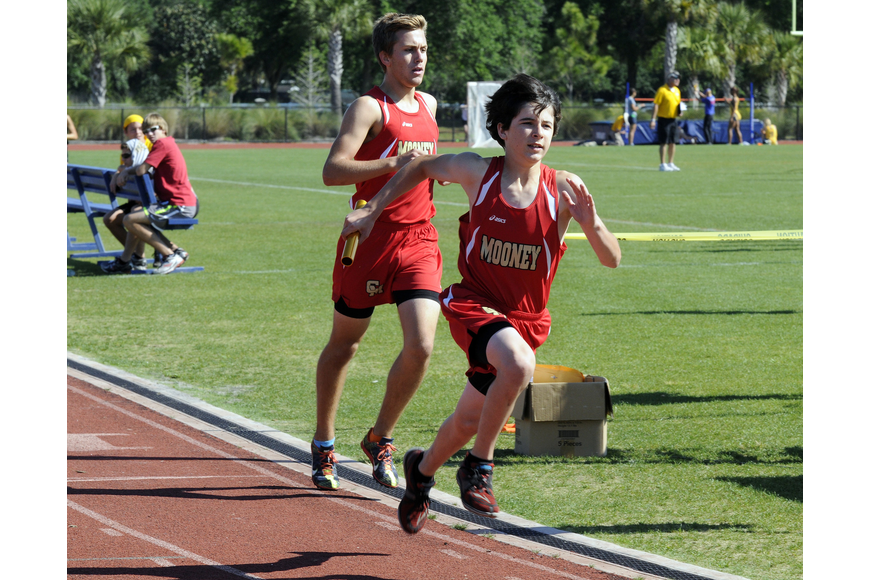 Cardinal Mooney's Adam Sage takes off in the boys 4x800-meter relay after receiving the exchange from Mitch Gannon.