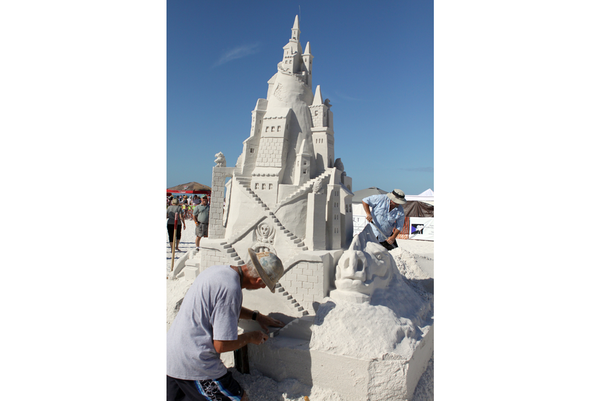 Ky Terrell and Andy Hancock work away at their sand sculpture on Saturday afternoon.