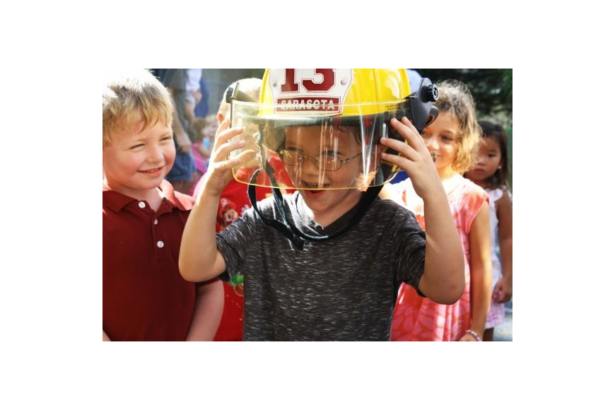 SIESTA KEY: Logan Lutz watches as Chance McArtor can barely support the weight of a firefighter helmet.