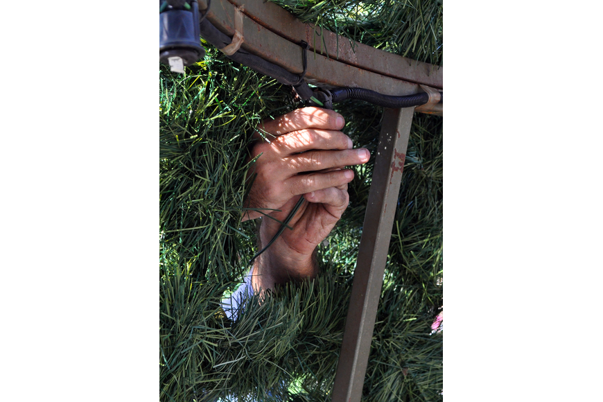 Hands come through from the outside of the tree to help connect some of the lights that go on the tree.