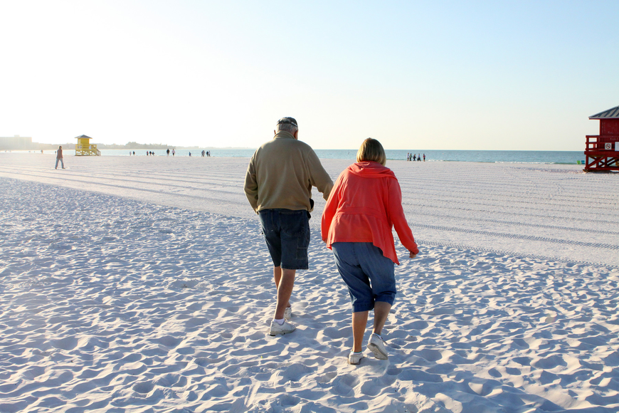 Don and Anita Glogovsky make their way down the beach for the Senior Beach Walk, Wednesday morning on Siesta Key Beach.