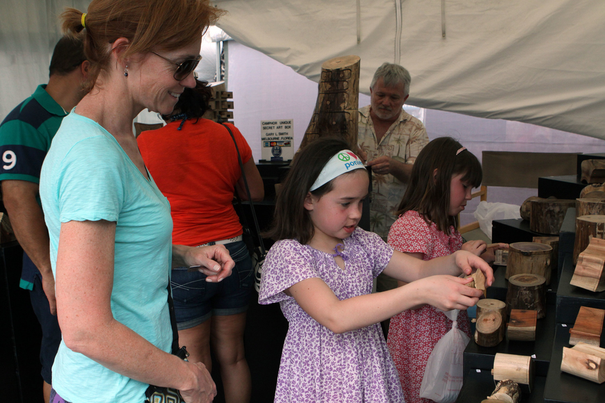 Mary Beth Canfield's daughters, Megan, 7, and Molly, 9, have fun finding all of the secret hiding places inside Camphor Unique Secret Art Boxes, Saturday, April 14, at Siesta Fiesta.