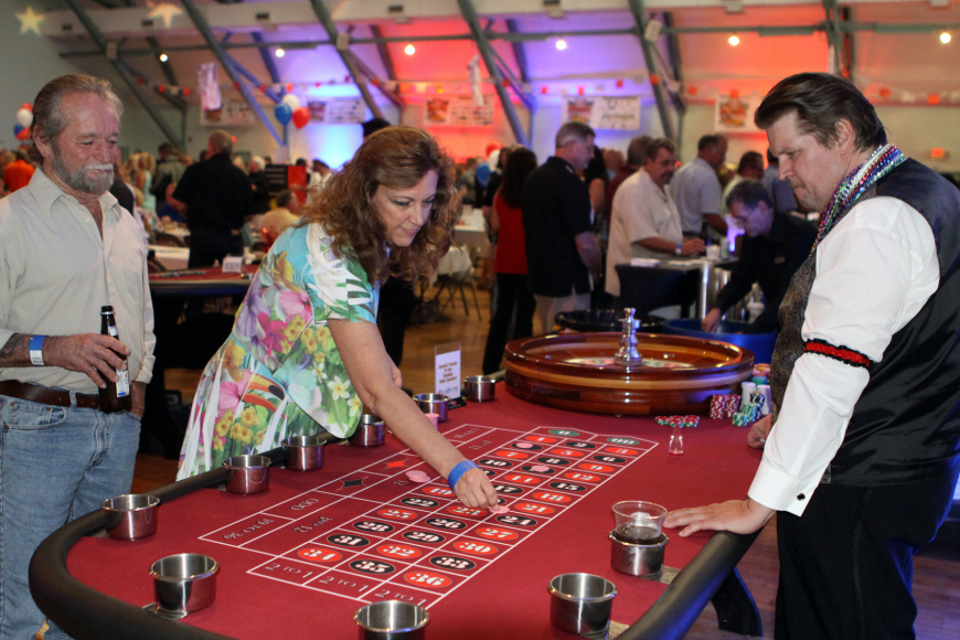 Shelly Brown has fun playing Roulette as her husband, Daniel, looks on, Saturday, June 23, at the Festival Kickoff Party for the 2012 Suncoast Super Boat Grand Prix Festival at the Sarasota Municipal Auditorium.