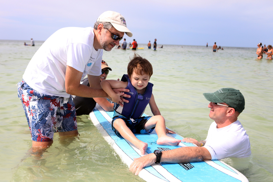 Andrew Burg along with Michelle Chrzczonowski and Bob Silverman help Nathan Burg, 3 ½, get comfortable on a surfboard Saturday, Sept. 15 during Hang 10 for Autism at Siesta Key Public Beach.