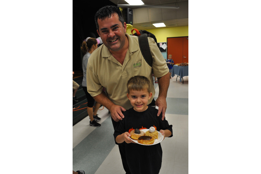 Keenan McRoberts, 5, made a face with his doughnuts. He is pictured with his father, Eric.