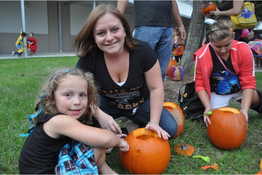 Chloe carves a pumpkin with her mom Marie Fisher.