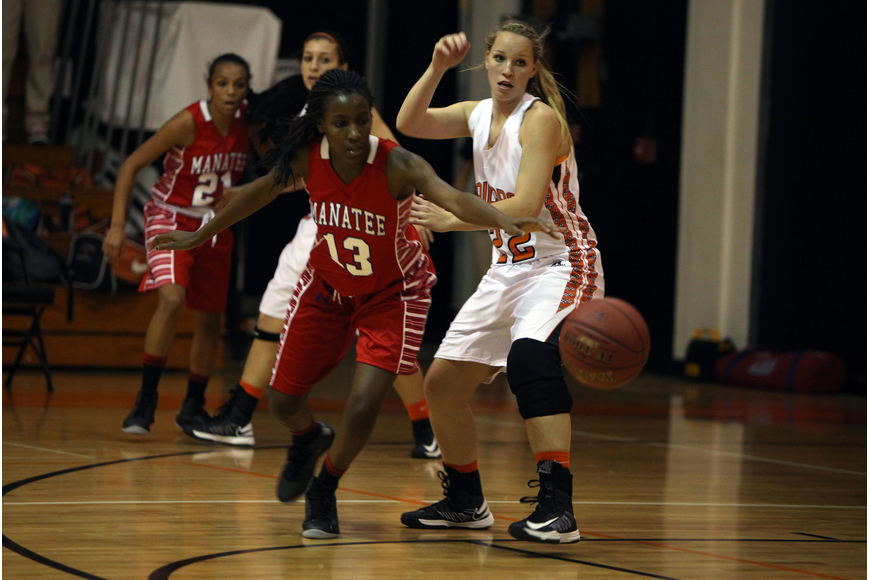 Manatee's Whitney Davis, No. 13, and Sarasota's Caylee Wallace, No. 22, try to beat one another to the ball.