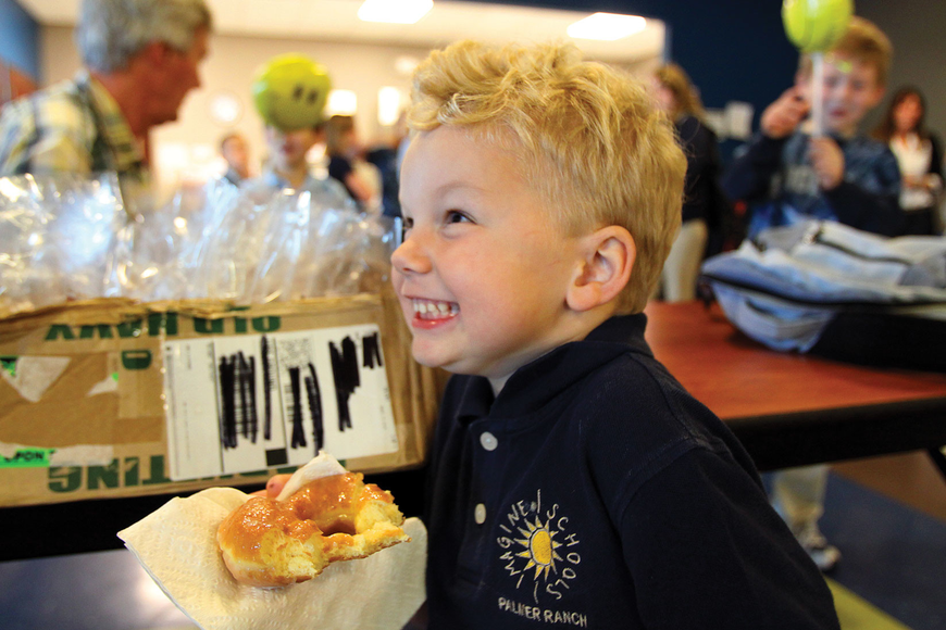 Blake Chamberlain, 5, gave his dad a sugary smile while enjoying a donut during Imagine School's Donuts with Dad breakfast.