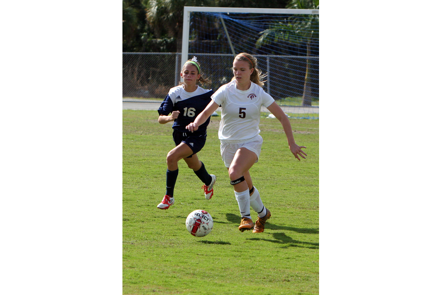 North Port's Alexis Egoville, No. 16, runs after Riverview's Rachel Easterling, No. 5.