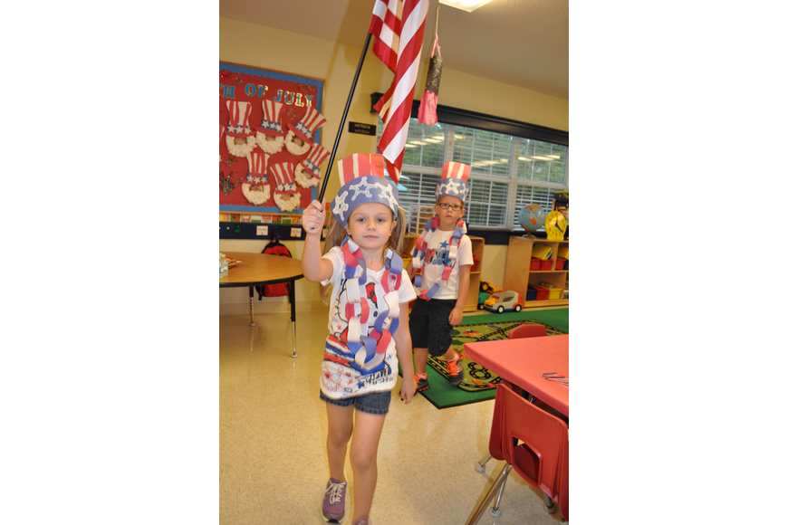 Five-year-old Tayler Snelling leads her classmates with the American flag.