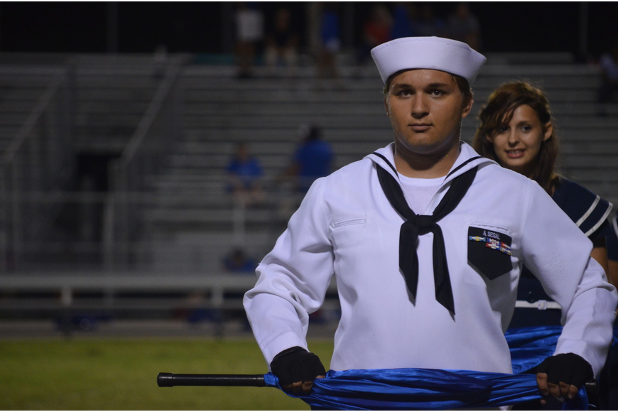 Junior Aaron Segal performs during halftime in the Color Guard.