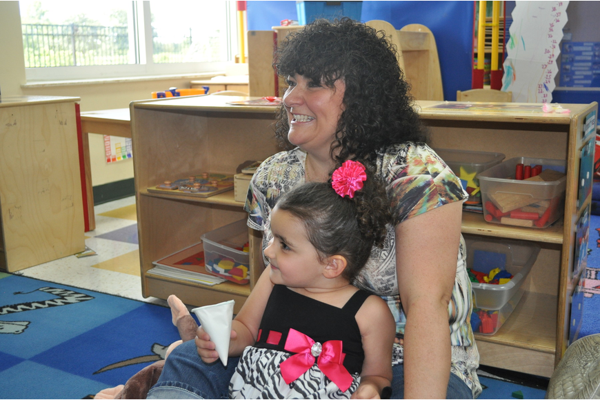 Christine Belville and her daughter, Rylee, 3, listened to a reading of Curious George.