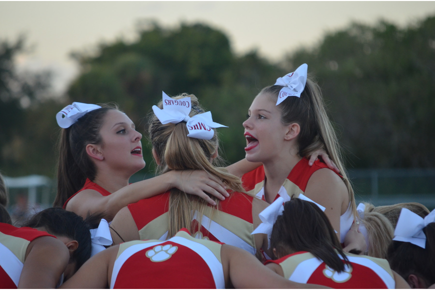 Cheer captain Summer Egly, 17, and co captain Savannah Savadel, 17, cheer for their team as they prepare to be lifted.