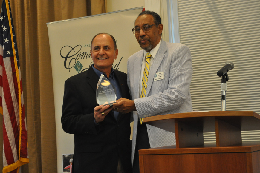 Colonel John W. Saputo, president/owner of Gold Coast Eagle Distributing and former Marine, accepted the 2013 C. John A. Clarke Humanitarian Award from Dr. Richard Wharton.