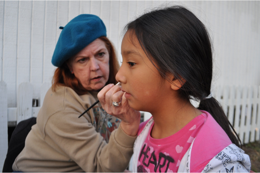 Art teacher Pat Knowlton adds glitter to the butterfly on the face of Desiree Delgado, 9.