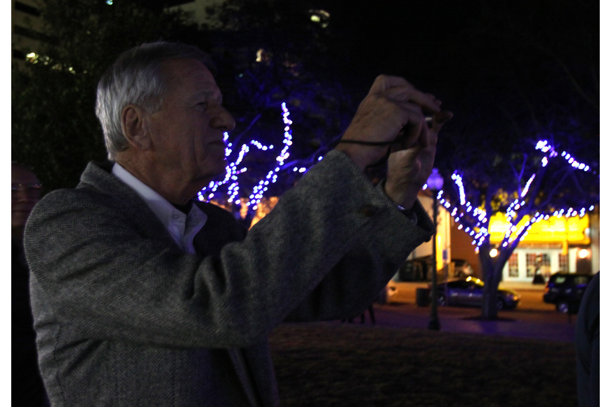 John Moran takes a photo of the tree lighting event on Friday in Five Points Selby Park. Moran was entrusted with managing the LED lighting project.