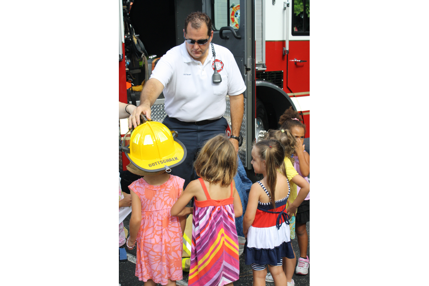 Fire Lieutenant Scot Gottschalk shows the children of St. Boniface Preschool what a fireman wears when he puts out a fire.