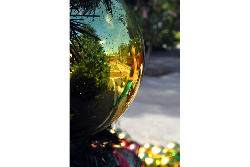 Pamela Scollay and part of St. Armands Circle is reflected in a gold ornament on the Christmas tree.