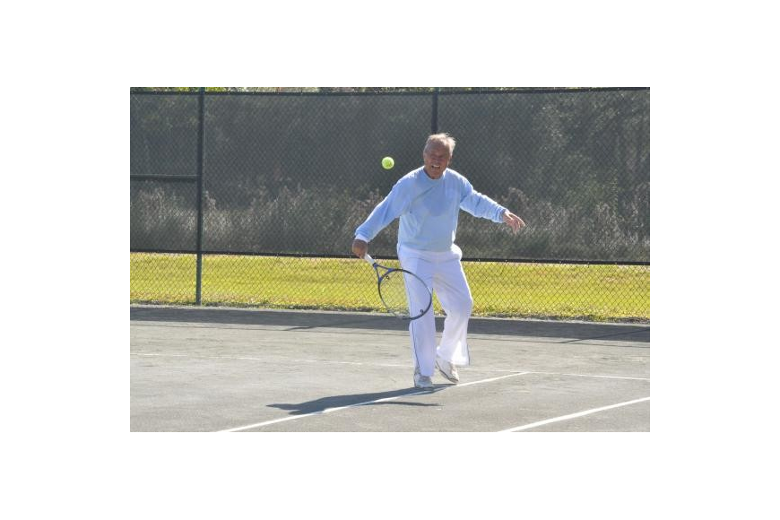 Jim Baker volleys a tennis ball. Photo by Mallory Gnaegy.