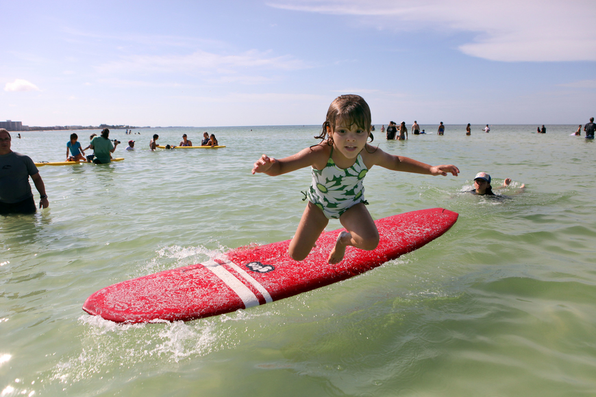 Brooke Decillis, 5, jumps off a surfboard and into the water Saturday, Sept. 15.