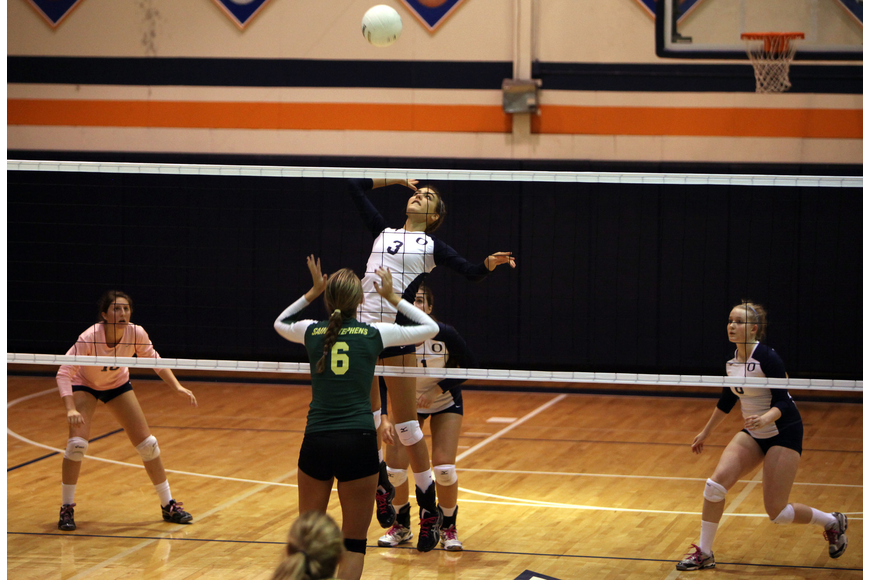 Gabriella Costa, No. 3, gets some air as she jumps up to spike the ball at Lauren Biach, No. 6.