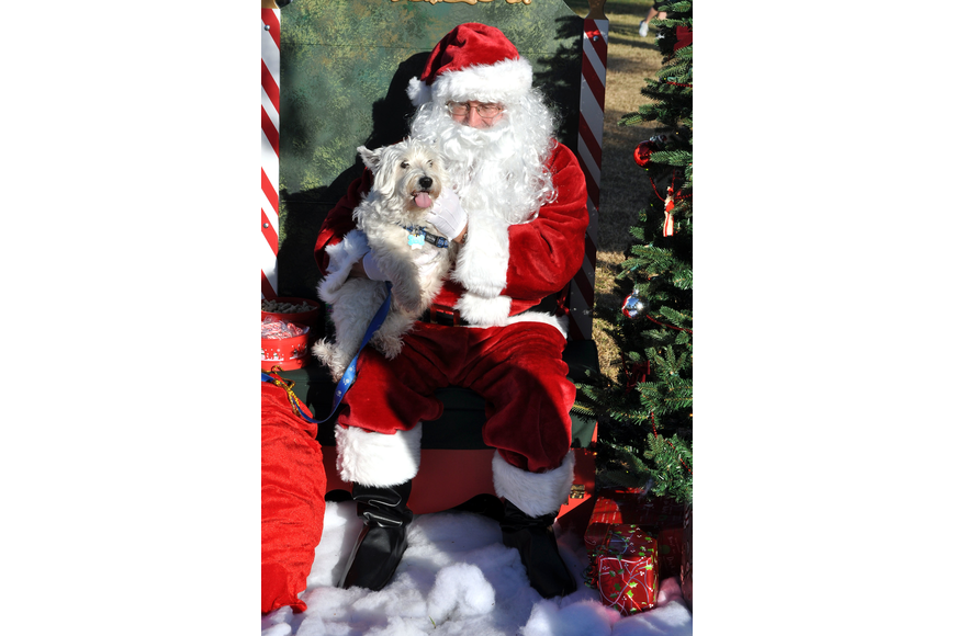 Chumsley, 11, smiles and sticks his tongue out while sitting with Santa Saturday, Dec. 1, at Payne Park.