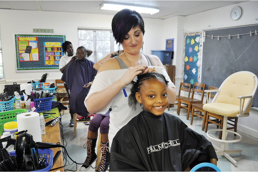 Cherie Diaz braids Markeyl Green's at Church of the Redeemer as part of the Hope Kids Community Day of Hope.