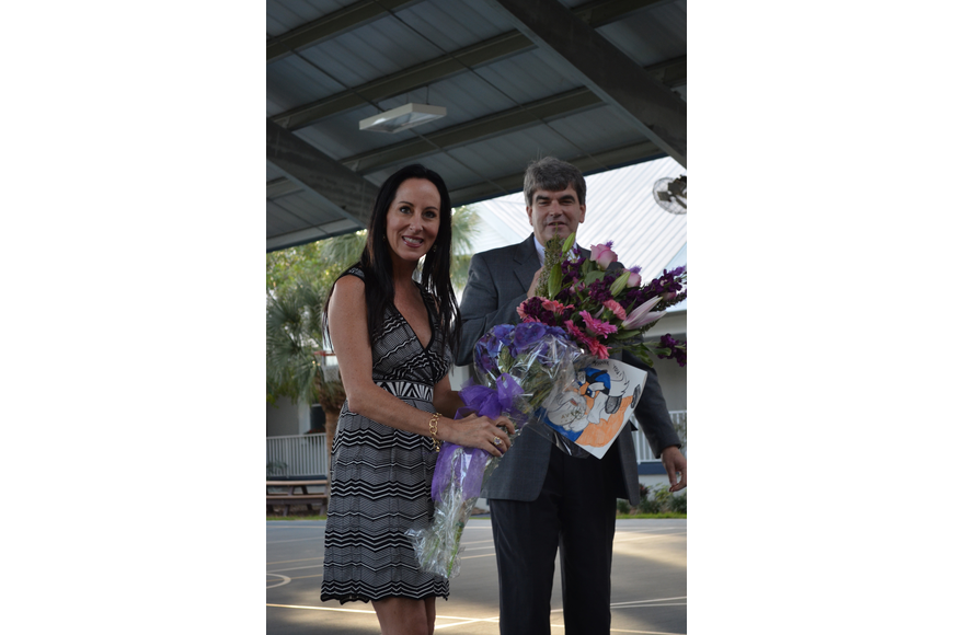 David Mahler gives Ashley Kozel flowers for her birthday and thanks her for donating funds for the Wellness Center.