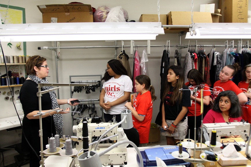 Susan Brothers, operations manager, shows the girls around the alterations room during their tour Wednesday, Feb. 20, of Saks Fifth Avenue.