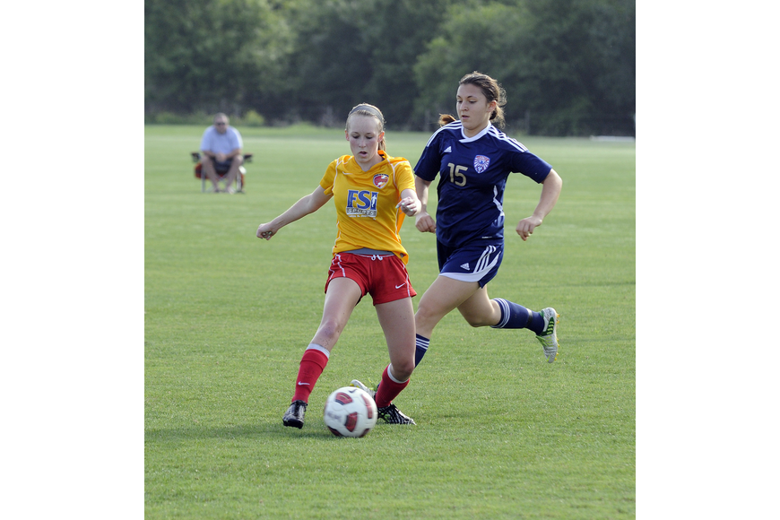 Clearwater Chargers Elite midfielder Delaney Tyl attempts to dribble the ball around a West Side Lady Eagles defender.