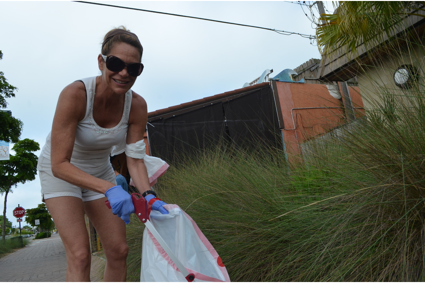 Lisa Batastini picks up trash in the Village Saturday, June 1. She has a home on Siesta Key but lives full time in New Jersey.
