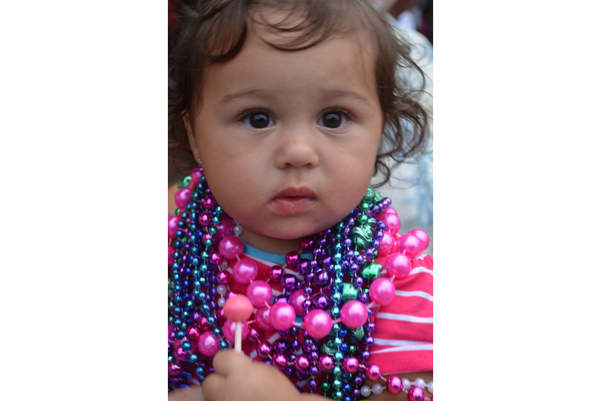 Mea Donahue, 15 months, collects beads and sucks on her lollipop during the parade.