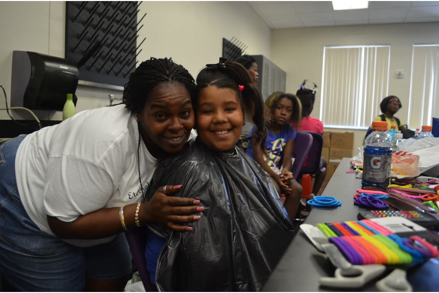 Denise Robins with Eternal Bread of Life Outreach ministries does 10-year-old Tatiana Johnson's hair.